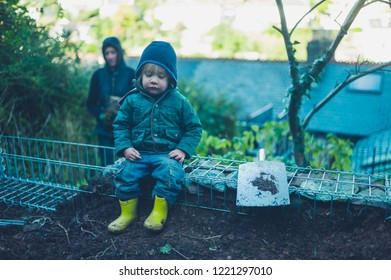 A little toddler is sitting on some gabians in a garden