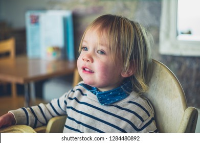 A little toddler is sitting at a table in a cafe