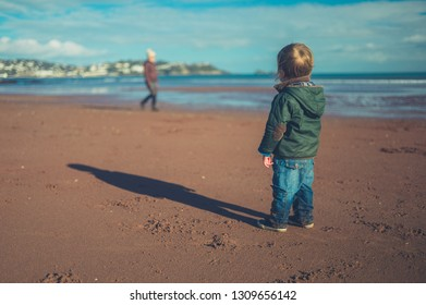 A little toddler is standing on the beach in winter