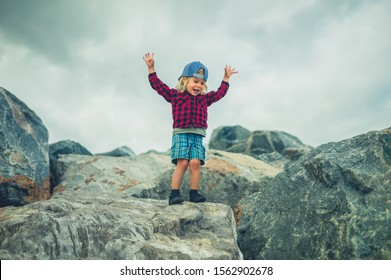 A little toddler is standing on a rock with his arms raised against a cloudy sky
