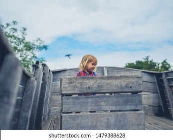 A little toddler is standing on a wooden ship