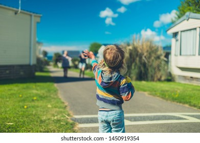 A little toddler is standing in a trailer park waving at his family