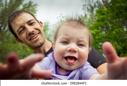 little toddler taking selfie with her daddy at a park in the summer with a shallow depth of field on daughter with bokeh