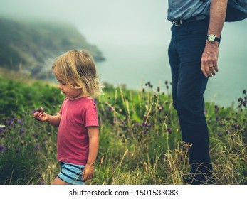 A little toddler is walking by the coast with his grandfather on a cloudy day. Authentic family lifestyle shot.