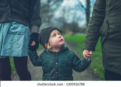 A little toddler is walking outdoors in a park with his mother and grandmother