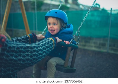 A little toddler wearing a helmet is on the swing in the playground