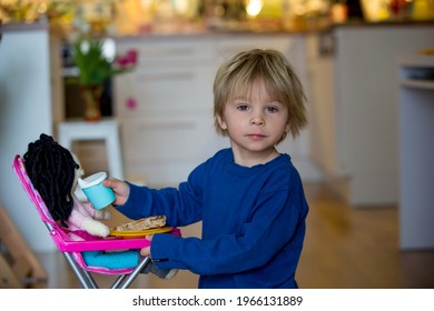 Little toddlerchild, boy, feeding his favorite doll, sitting in doll chair at home