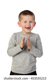 Little toothless boy with wide happy smile on face joyfully clapping hands. Portrait on gray background
