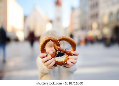 Little tourist holding traditional bavarian bread called pretzel in Munich, Germany. National cuisine concept