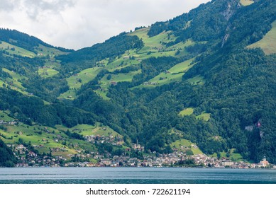 Little town on lake Lucerne shore, with picturesque mountain landscape