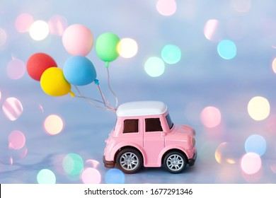 Little toy car with colorful ballons and bokeh lights