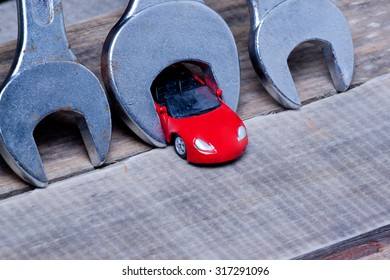 little toy car and wrenches.metaphor. car maintenance