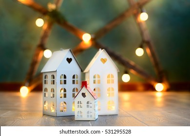 little toy Christmas houses with a burning light inside is on blurred green background. Real estate, holiday, xmas, miniature