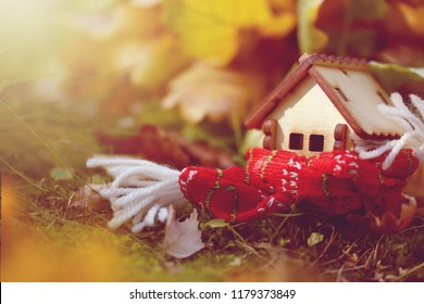 little toy house wrapped scarf in autumn forest, illuminated by sun, close-up photo, selective focus