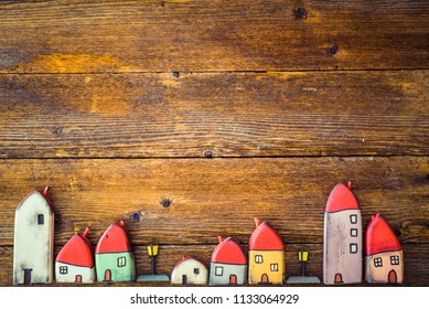 Little toy, painted wooden houses standing over a wooden background