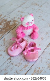 Little toy-teddy bear and children's shoes on a wooden background.