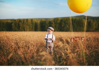 little traveler boy keeps a telescope next to the balloon in a field