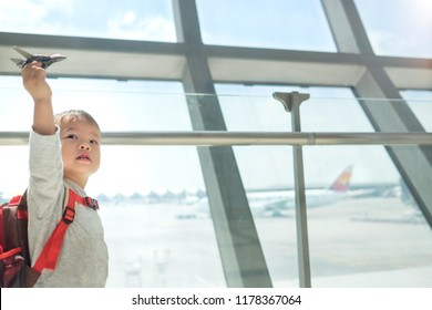 Little traveler, cute smiling little Asian 2 years old toddler boy child having fun playing with airplane toy while waiting for his flight at gate in terminal at airport, Traveling with kid concept