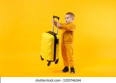 Little traveler tourist kid boy 3-4 years old isolated on yellow orange wall background studio. Passenger traveling abroad to travel on weekends getaway. Air flight journey concept. Mockup copy space
