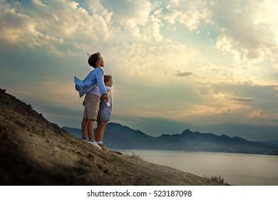 Little travelers are on the edge of a mountain by the sea and watch the sunset. Children and nature.
