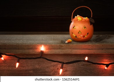 Little Trick or Treat Halloween Pumpkin filled with candy corn on a rustic wood shelf with row of orange lights and dark background above.  Horizontal with copy space.