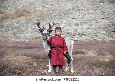 Little Tsaatan boy in traditional deel posing with a baby reindeer. Khuvsgul, Mongolia.