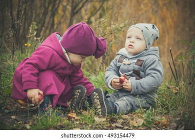 Little twins boy and girl outdoor in autumn park