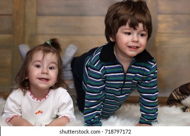 Little twins are lying on the floor and smiling