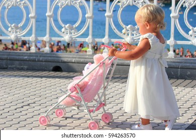Little two year old girl walking in the park with a baby carriage and a pink fluffy bunny