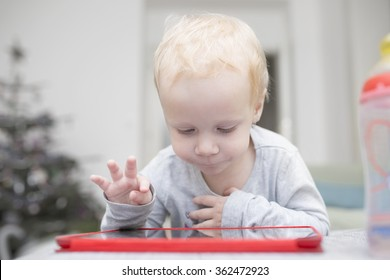 Little two years girl uses a tablet on a sofa