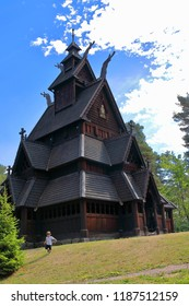 Little two years old boy running and playing in front of the Gol Church, a stave church originally built in Gol city, but now located in the Norwegian Museum of Cultural History at Bygdøy in Oslo.