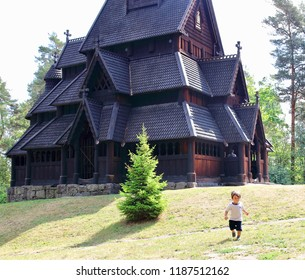 Little two years old boy running and playing in front of the Gol Church, a stave church originally built in Gol city,but now located in the Norwegian Museum of Cultural History at Bygdøy,Oslo,Norway.
