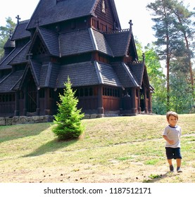 Little two years old boy running and playing in front of the Gol Church, a stave church originally built in Gol city, but now located in the Norwegian Museum of Cultural History at Bygdøy,Oslo,Norway.