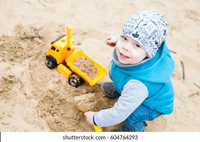 Little, two years old boy, playing truck toy in sandbox. He refill of sand his trolley truck and have fun because of that.