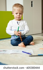Little, two years old boy, playing crayons on the floor