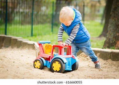 Little, two years old boy is playing in sandbox using a big excavator.