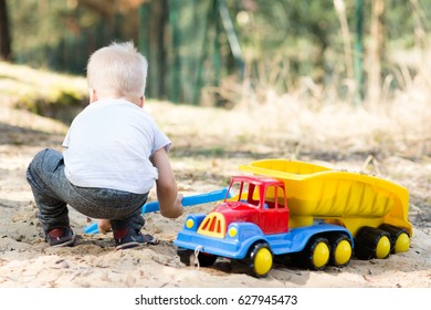 Little, two years old boy, playing plastic construction vehicles toys at forest on sand
