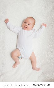 Little two-month baby boy in white romper on a white textile background