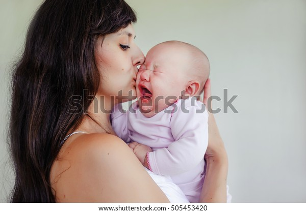 The little two-month girl cries at the mother on hands. Mother and daughter. children's cry and tears. Mom comforts a newborn baby.
