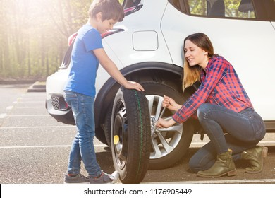 Little tyre mechanic helping mom to change a wheel
