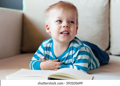 Little, unhappy and disappointed, two years old boy lying on his belly on the sofa, with open book in front of him.
