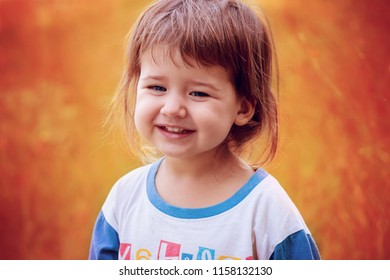 Little unkempt baby girl smiling on an orange background, open air