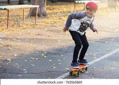 Kleiner urbaner Junge mit Penny-Skateboard. Junge Kinder fahren im Park auf einem Skateboard. City Style. Städtische Kinder. Kind lernt Penny Board reiten