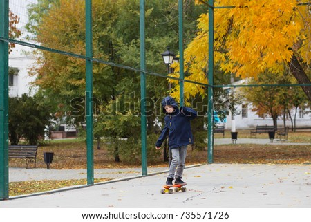 0866b28f919 Little urban boy with a penny skateboard. Kid skating in an autumn park.  City