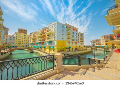 Little Venice with canals connected by bridges in venetian style. Colorful houses in picturesque Qanat Quartier icon of Doha, Qatar at daylight. Venice at the Pearl, Persian Gulf, Middle East.