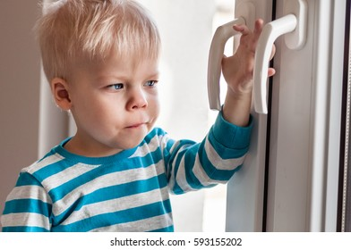Little, very sad, two years old boy standing by the window and waiting for something