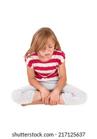 A little very unhappy girl sitting in her track pants and striped top on the floor and crying, isolated on white background.