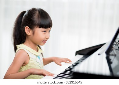 Little Vietnamese girl playing the piano at home