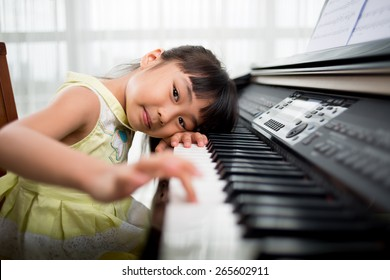 Little Vietnamese girl playing synthesizer and looking,at the camera buttons are digitally modified