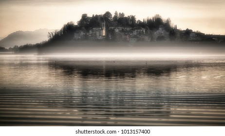 The little village of Biandronno with fog over the lake of Varese in a winter afternoon